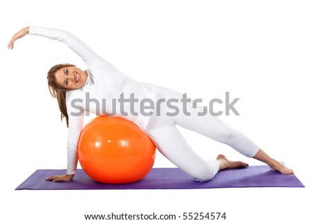 Fit woman exercising with a pilates ball - isolated over a white background - stock photo
