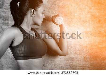 Fit woman exercising with weights on the background of a concrete wall in the gym. Healthy lifestyle concept. - stock photo