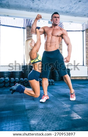 Fit woman hanging on a hand of muscular man at gym - stock photo