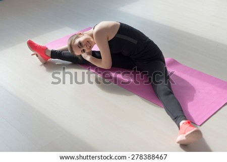 Fit woman high body flexibility stretching her leg to warm up doing aerobics gymnastics exercises at home or yoga class. - stock photo