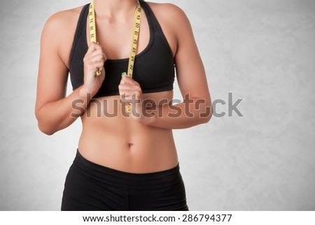 Fit woman holding a measuring tape around her neck, isolated in a grey background - stock photo