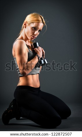 Fit woman holding weights - stock photo