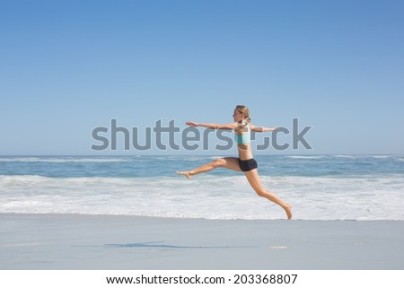 Fit woman jumping gracefully on the beach on a sunny day - stock photo