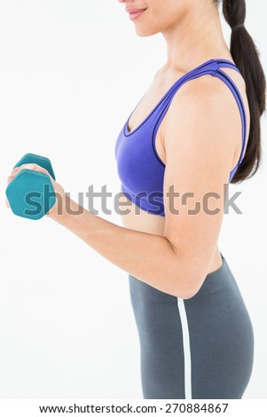 Fit woman lifting dumbbell on white background - stock photo