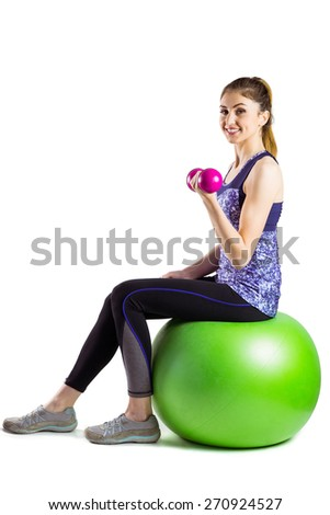 Fit woman lifting dumbbell sitting on ball on white background - stock photo
