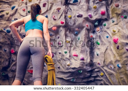 Fit woman looking up at rock climbing wall at the gym - stock photo