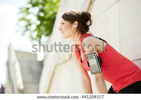 Fit woman rest after jogging and listening music. - stock photo