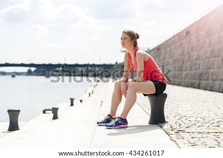 Fit woman resting after run by the river. Jogger. - stock photo