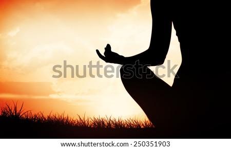 Fit woman sitting in lotus pose against orange sunrise - stock photo
