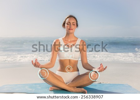 Fit woman sitting in lotus pose on the beach against fitness interface - stock photo