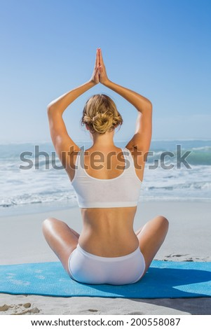 Fit woman sitting in lotus pose on the beach on a sunny day - stock photo