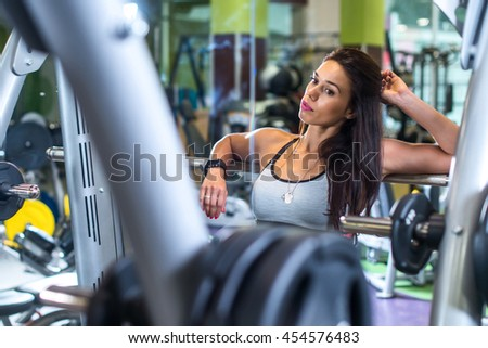 Fit woman standing in front of large mirror at the gym - stock photo