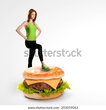 Fit woman standing on a cheeseburger - stock photo