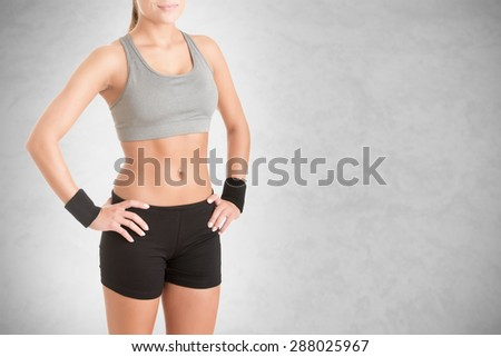 Fit woman standing with her arms at her waist, isolated in grey - stock photo