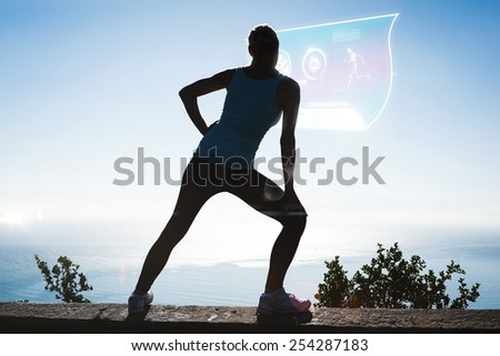 Fit woman stretching her legs looking out to sea against fitness interface - stock photo
