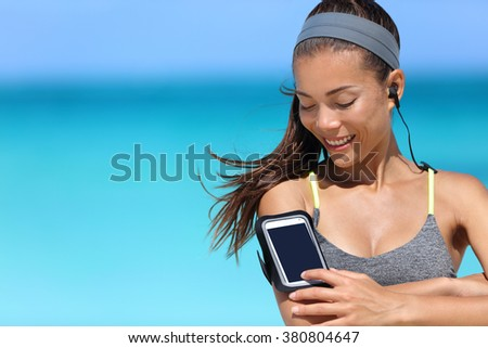 Fit woman using smartphone fitness app on armband. Young Asian female runner touching the display touchscreen on sports arm strap with mobile phone for listening to music or as activity tracker. - stock photo
