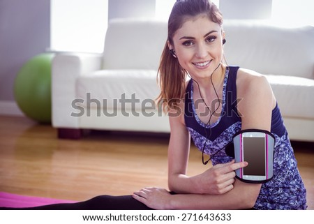 Fit woman using smartphone in armband at home in the living room - stock photo