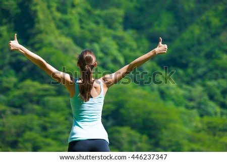 Fit woman with thumbs up enjoying the great outdoors.  - stock photo