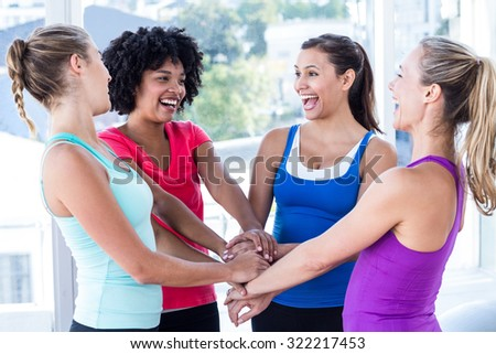 Fit women enjoying while holding hands at fitness studio - stock photo