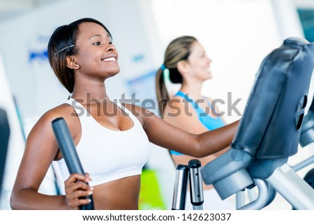 Fit women exercising at the gym on an x-trainer - stock photo