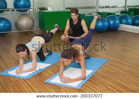 Fit women in pilates position with trainer watching at the gym - stock photo
