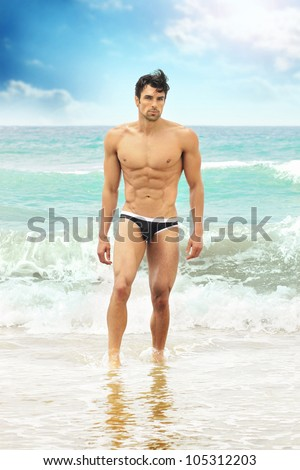 Fit worked-out man walking out of ocean onto beach with sky background and reflection in foreground - stock photo