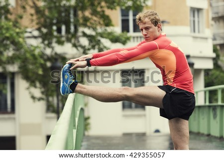 Fit young athletic male stretching outside on bridge - stock photo