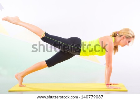 Fit young blonde pilates instructor showing different exercises with basic sport equipment including  yoga mat - stock photo