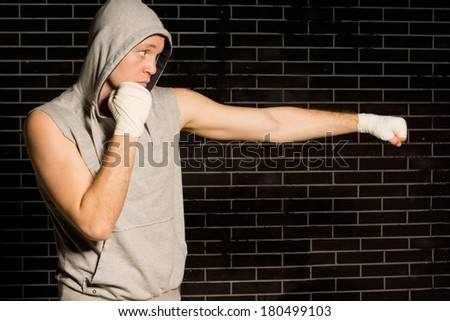 Fit young boxer working out throwing a punch with his bandaged fist against a dark brick wall with copyspace, side view - stock photo
