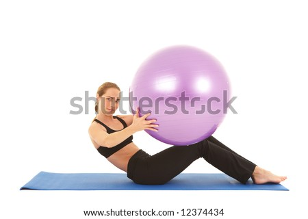 Fit young brunette pilates instructor showing different exercises on a white background with basic pilates equipment including a ball and yoga mat. White background, not isolated - stock photo