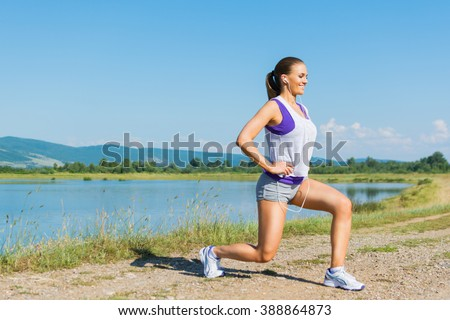 Fit young Caucasian blonde teenage girl smiling, doing squats, outdoors on sunny summer day in nature by the lake. Fit young woman working out doing leg workout outdoors. Medium retouch, natural light - stock photo