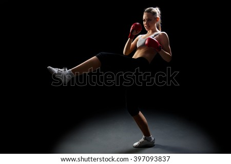 Fit, young, energetic woman kickboxing, black background - stock photo