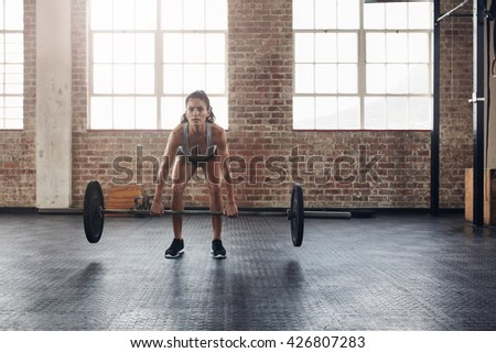 Fit young female holding a barbell in her hands. woman lifting heavy weights in gym. - stock photo