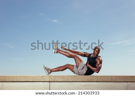Fit young guy doing stretching workout outdoors. Muscular young fitness model exercising against sky. - stock photo