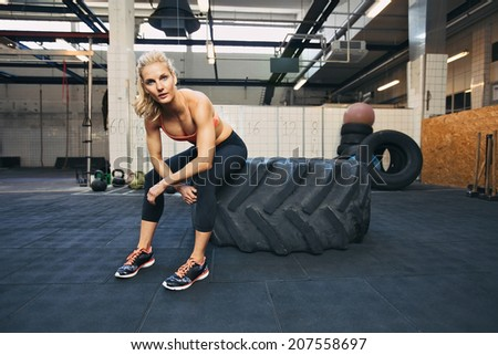 Fit young lady sitting on a big tire after her workout. Woman taking rest after exercise at gym. - stock photo