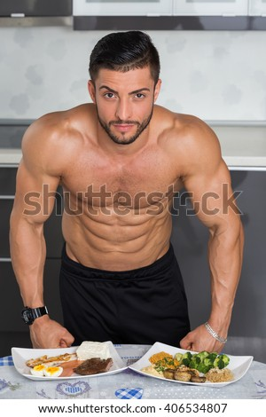 fit young man bodybuilder in the kitchen; animal versus plant proteins: plate with beef, eggs, salmon, cheese and chicken grill and another with nuts, mushrooms, broccoli, lentil, hummus and quinoa - stock photo