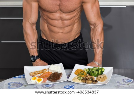 fit young man. bodybuilder in the kitchen; animal versus plant proteins: plate with beef, eggs, salmon, cheese and chicken grill and another with nuts, mushrooms, broccoli, lentil, hummus and quinoa - stock photo