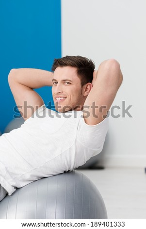 Fit young man doing pilates exercices at the gym balancing over a gym ball turning to smile at the camera - stock photo