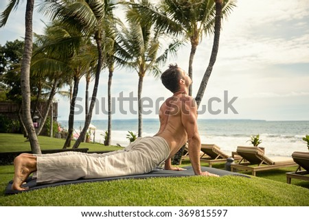 fit young man doing the cobra pose in nature near the ocean - stock photo