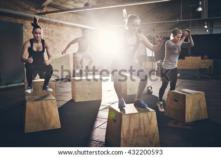 Fit young people doing box jumps as a group in a gym - stock photo