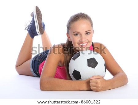 Fit young teenage athlete girl lying on the floor holding soccer ball with beautiful smile wearing pink vest and denim shorts. Full body shot against white background. - stock photo