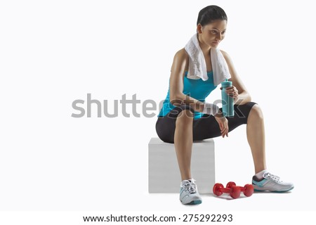 Fit young woman holding water bottle while lost in thoughts over white background - stock photo