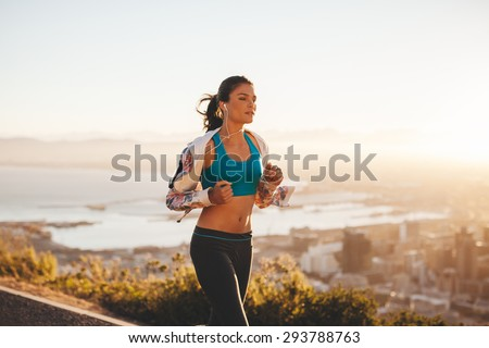 Fit young woman jogging outdoors. Female athlete on morning run with bright light. - stock photo