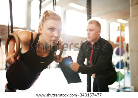 Fit young woman with her personal fitness trainer in the gym exercising with gymnastic rings - stock photo