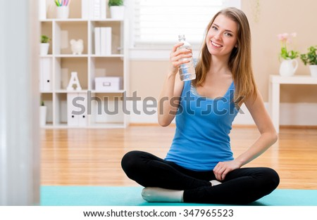 Fit young woman with water bottle ready for yoga at home - stock photo