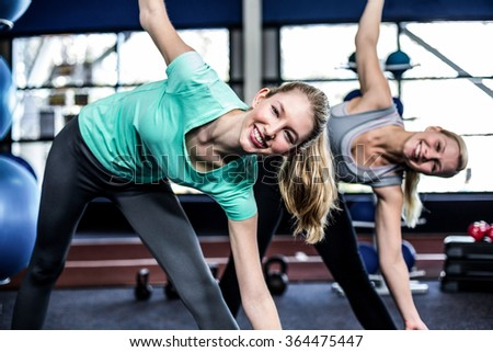 Fit young women stretching in the gym - stock photo