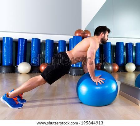 Fitball abdominal push ups Swiss ball man pushup at fitness gym - stock photo