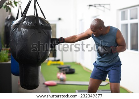 fitness african man training with punch bag in gym - stock photo