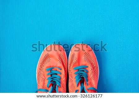 Fitness and gym workout concept. Healthy lifestyle background with sport training shoes close up and blue copy space. - stock photo