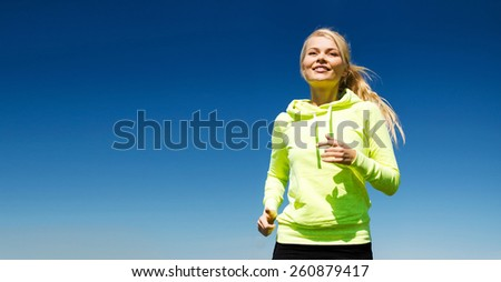 fitness and lifestyle concept - female runner jogging outdoors - stock photo